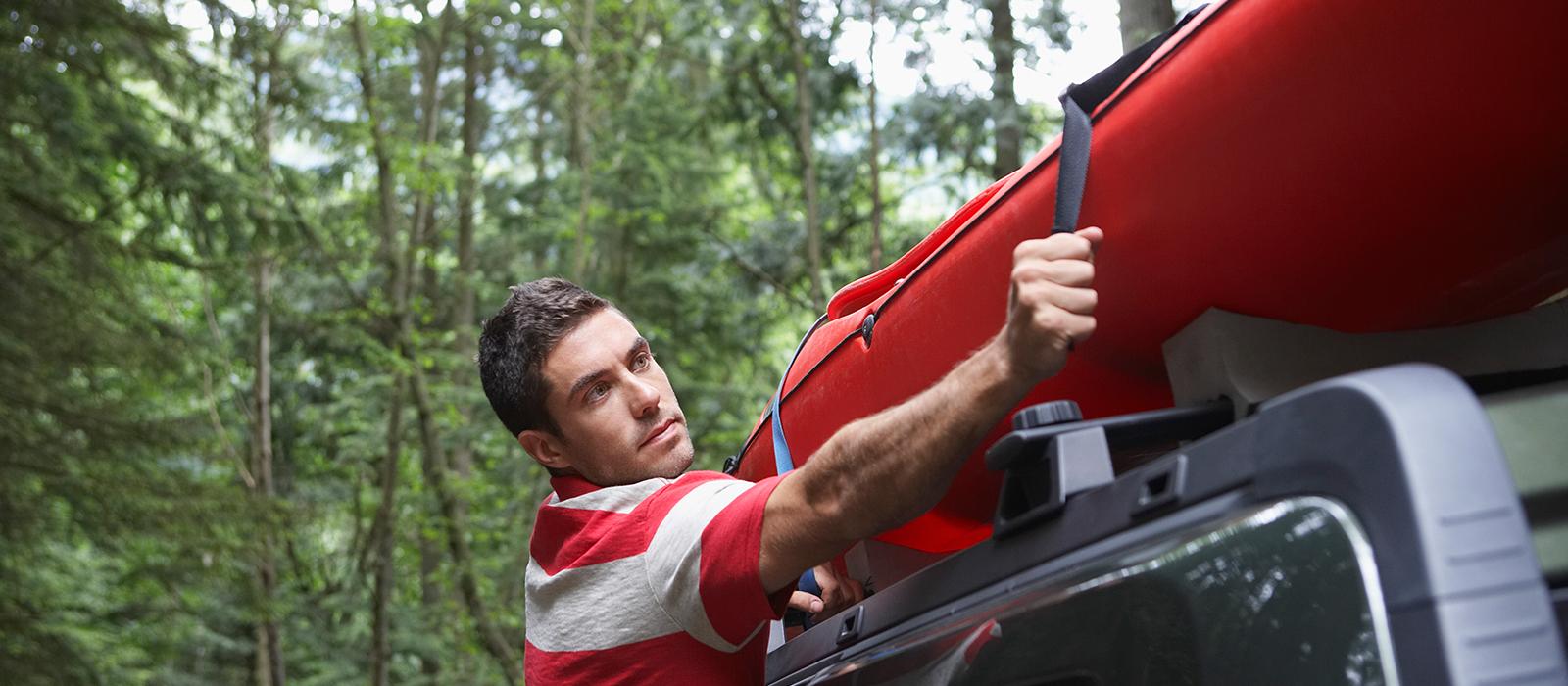 Man fastening a kayak to his car roof